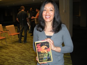 "Estella Gonzalez holding ""Latinos in Lotusland: An Anthology of Contemporary Southern California Literature"" which includes her short story ""Act of Faith"""